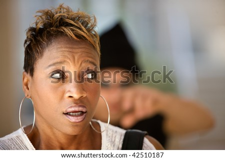 African-American woman being stalked by a criminal - stock photo