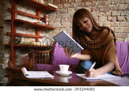 African American woman calculating her bills.  - stock photo