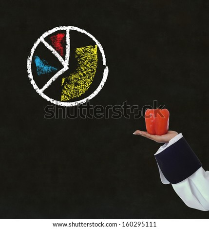 african american woman chef holding a pepper with chalk pie chart on blackboard background - stock photo