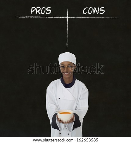 african american woman chef holding soup bowl with chalk pros and cons on blackboard background - stock photo