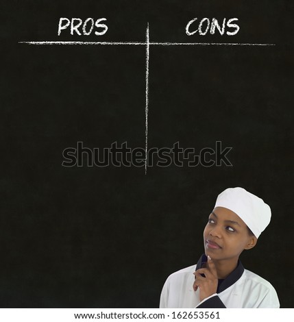 african american woman chef thinking with chalk pros and cons on blackboard background - stock photo