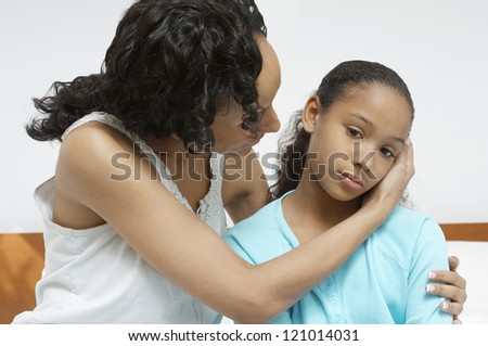 African American woman comforting sick daughter at home - stock photo