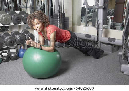 African American woman doing plank exercise on a gym ball - stock photo