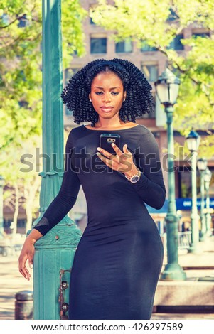 African American Woman Fashion in New York. Wearing long sleeve, slim, fitted dress, wristwatch, black girl with braid hairstyle standing by light pole on street, reading, texting on cell phone. - stock photo