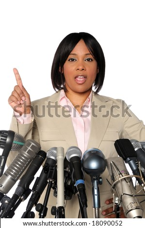 African American woman giving speech behind microphones during press conference - stock photo