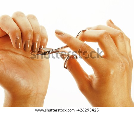 african american woman hands making no qualified manicure, pedicure to herself isolated with tools, bad nails - stock photo