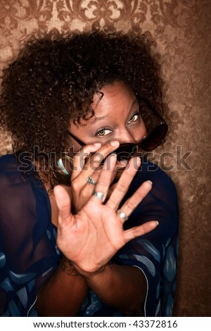 African American Woman Hiding from Paparazzi Photographer
