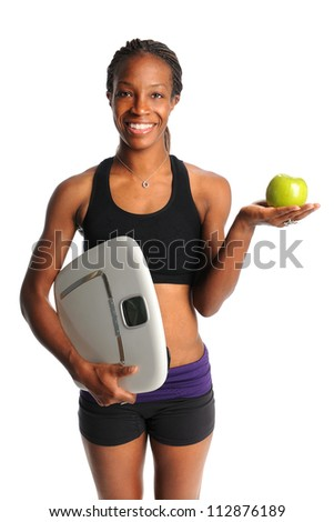 African American woman holding apple and scale isolated over white background - stock photo