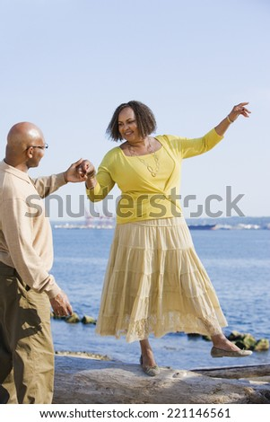 African American woman holding husband's hand for balance - stock photo