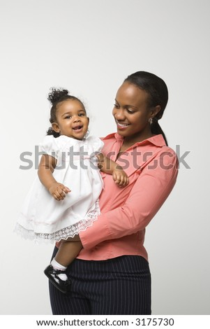 African American woman holding infant girl standing against white background. - stock photo