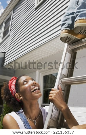 African American woman holding ladder - stock photo