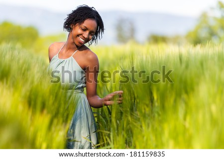 African American woman in a wheat field - African people - stock photo