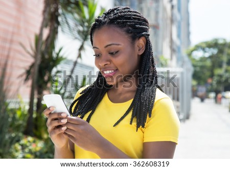 African american woman in a yellow shirt texting message with mobile phone - stock photo
