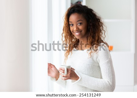 African American woman in her living room drinking holding a coffee tea mug - Black people - stock photo