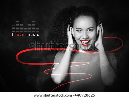 African American woman listening to music in headphones on black background - stock photo
