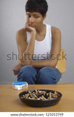African American woman looking at full ashtray on table - stock photo