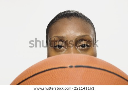 African American woman looking over basketball - stock photo