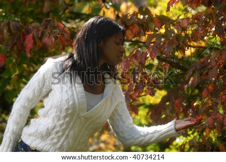 African-American woman looks at the different colors on the leafs - stock photo