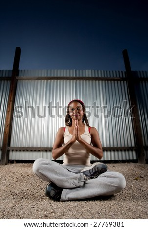 African-American woman meditating in front of corrugated metal - stock photo
