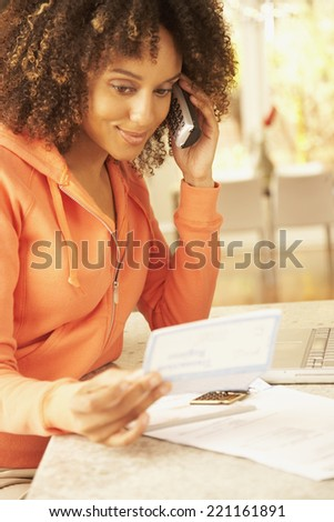 African American woman paying bills - stock photo