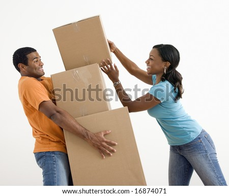 African American woman placing boxes on large stack man is holding. - stock photo