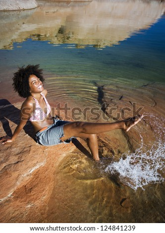 African American woman playing with water on riverside - stock photo