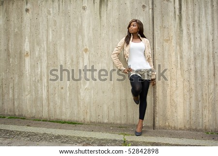 African American woman posing in front of concrete wall - stock photo