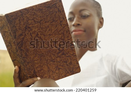 African American woman reading book outdoors - stock photo