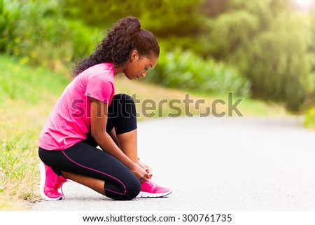 African american woman runner tightening shoe lace - Fitness, people and healthy lifestyle - stock photo
