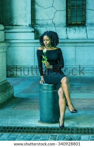 African American Woman seeking love in New York. Wearing long sleeve, off shoulder dress, holding white rose, a girl sitting on street, crossing legs, looking at you. Filtered look with cyan tint.