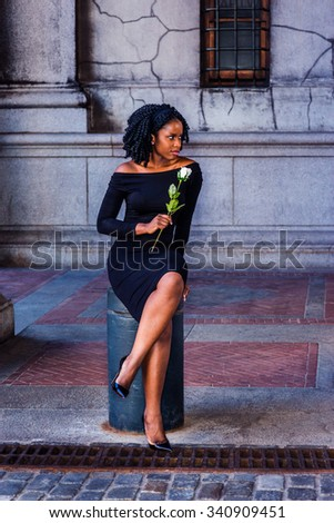 African American Woman seeking love in New York. Wearing long sleeve, slim, off shoulder dress, holding white rose, a young black girl sitting on street, looking away.  Filtered look with purple tint. - stock photo