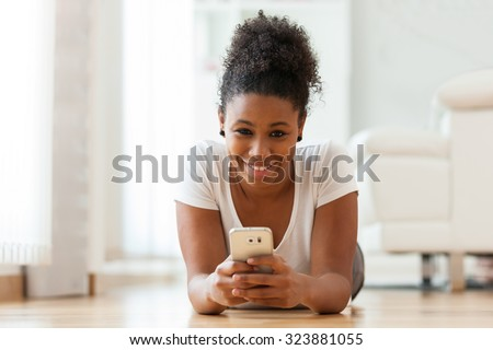 African American woman sending a text message on a mobile phone - Black people - stock photo