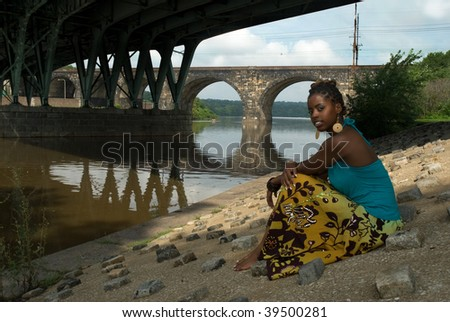 African American woman sits and relaxes by the river front