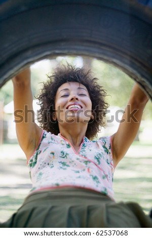 African American woman sitting in tire swing - stock photo