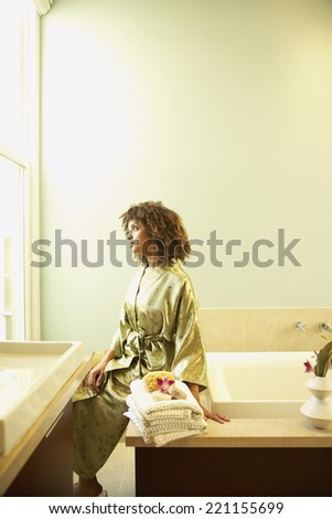 African American woman sitting on bathtub - stock photo