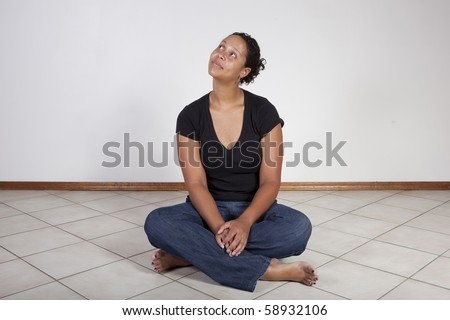 African American woman sitting on floor, looking up - stock photo