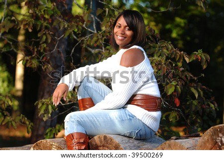 African-American woman sitting on log smiling - stock photo