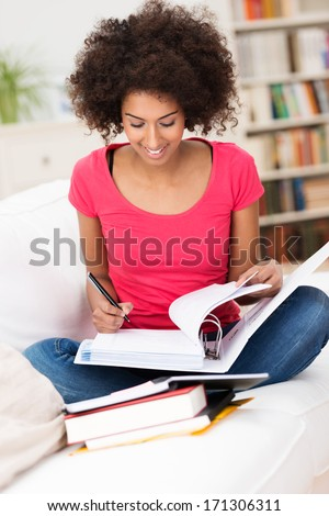 African American woman sitting on the sofa in the lotus position while studying hard and taking notes from the books, with bookshelves in the background - stock photo