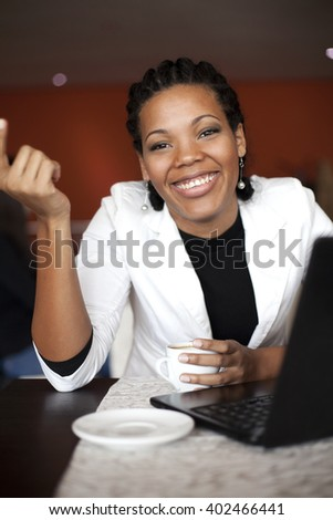 African american woman smiling in front of the laptop.