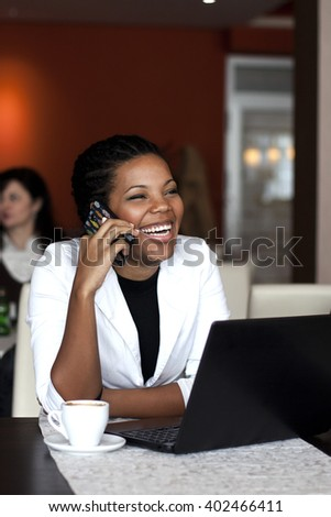 African american woman smiling in front of the laptop, speaking on the mobile phone.  - stock photo