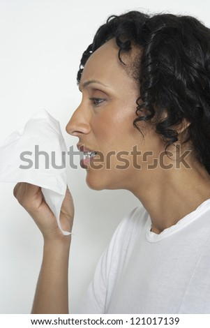 African American woman sneezing into tissue - stock photo