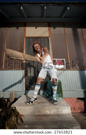 African American woman swinging a board on her front porch