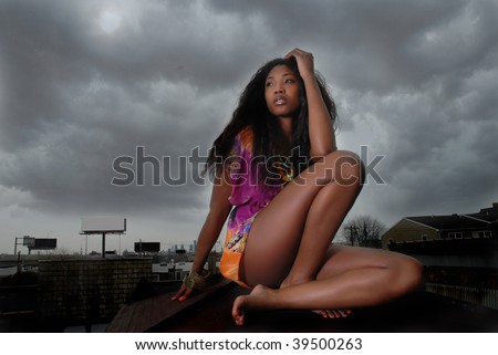 African American woman thinking as she stares, as she leans on her arms - stock photo