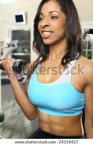 african american woman training or exercising in gym, doing weight lifting. very slight noise on bottom left area - stock photo
