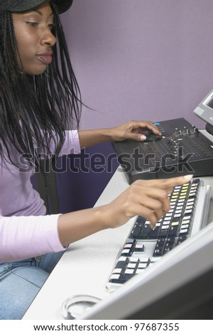 African American woman using computer and recording equipment - stock photo