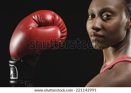 African American woman wearing boxing glove - stock photo