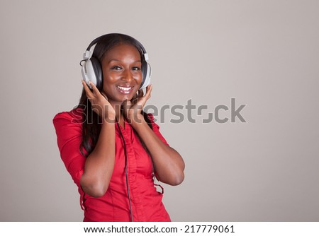 African American woman with American Indian heritage in a red shirt listening to music with vintage 1970s headphones - stock photo