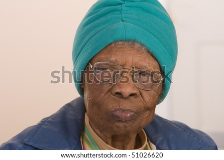 African American woman with glasses looking to the side. - stock photo