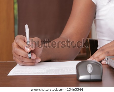 African American woman writing on a piece of paper near a workstation - stock photo