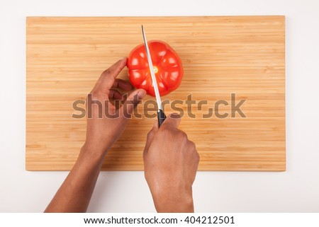 African  American womans hand slicing a tomatoe - Flat lay - stock photo